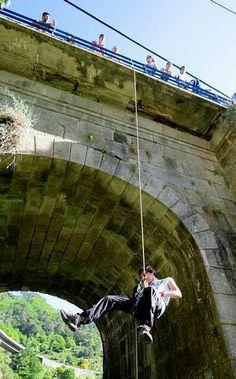 Colgados para aprender montañismo en el puente de Os Peares