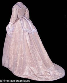 "1867 lady's lilac colored silk taffeta three piece gown, self fabric buttons, an ornate collar elaborate bowed and fringed cuffs to the modified pagoda sleeves. A separate matching waist sash with a back bow with decorative buckle and a three part split tail. A gored front and a cartridge pleated back to the unlined skirt with a transitional bustle, a deep crinoline faced hem and a silk satin floor brush. 18"" from shoulder to shoulder 36"" bust 24"" waist and 59"" from shoulder to front hem"