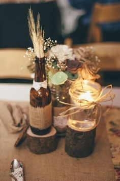 center pieces: 3 different heights of small wood stumps, with a beer bootle and wheat, medium mason jar with floating candle, and bigger mason jar with burlap, felt, and babies breath flowers. Small sliver stump with table number carved in it.