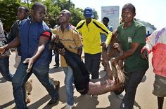 Protestors carry an injured man after he was shot by police in the western city of Kisumu, Kenya, during demonstrations by opposition supporters on June 6, 2016.