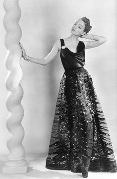 Liz Gibbons in black satin slip evening dress with net overlay embroidered in paillettes by Vionnet, jewelry is aquamarine ring and diamond clip and bracelets by Tiffany, photo by Martin Munkacsi, Harper's Bazaar, Nov. 1937