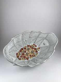 Wonderfully delicate porcelain basket by Romanian pottery, Camina. This gorgeous basket is intricately designed and painted, no detail left behind. It is adorned with gold accents and hand painted orange and yellow flowers. Would be a lovely piece of home decor or table center piece. Basket Dimensions: 11 5/8 in. long 6 3/4 in. wide 4 in. to tallest point For more information about our mission to create a circle of giving in our community, please visit our website at www.brownroo...