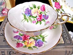 OFFERING THIS PRETTY TEA CUP AND SAUCER MADE BY PARAGON, SUPER DESIGN AND COLORS ON THE FLOWERS SWEET PEAS WIDE MOUTH TEACUP TRIMMED IN GOLD AND FANCY HANDLE FOOTED BASE MADE OF A FINE BONE CHINA WITH NO WEAR AND NO FADING AND NO CRAZING MADE AROUND THE LATE 1930S FOOTED BASE PLEASE