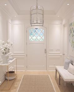 Foyer. Entryway. Millwork. Wisteria console. Benjamin Moore simply white.Circa lighting. Arch top medium lantern by E.F. Chapman , Belly basket. Sea grass rug. Floral art. front door diamond pane. Hamptons style. Coastal style. Foyer bench