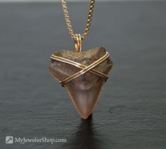 This shark tooth has been securely and beautifully wrapped with gold filled wire. It hangs nicely and is bound to start a conversation. Available on Etsy.