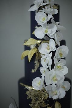 Midnight-blue wedding cake adorned with gold foiling and intricate sugar orchids | Victoria Made