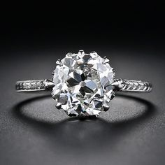 This gorgeous Edwardian-era solitaire diamond engagement ring, circa 1915, elegantly presents a 2.90 carat antique cushion-cut diamond. The glorious diamond dazzles solo from an exquisitely detailed platinum engagement ring adorned with a flour d'lys motif gallery and delicate hand engraving throughout. Understated elegance par excellence.