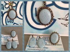 Conjunto con base metálica en color bronce y cadena bronce de 60 cm., cabuchón de arcilla polimérica en azul bebe. Colgante, pendientes y anillo ajustable.