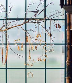 En stor gren i et vindue pyntet til jul med KONCIS kageforme