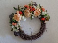This 18 in. grapevine wreath is adorned with graceful camellias, small rose buds, calla lilies, and other accent flowers and berries in shades