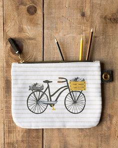 Bicicletta Large Zipper Pouch - A large zipper pouch made from sturdy 100% cotton is perfect for storing drawing supplies, small accessories, travel essentials and more. A metallic zipper keeps contents secure, while a grommet tab adds convenience. A whimsical bicycle carrying the day's newspapers pedals through the city against a striped background. Striped Background, Travel Essentials, Zipper Pouch, Travel Style, Travel Bags, Cosmetic Bag, Craft Supplies, Zip Around Wallet, Tote Bag