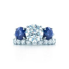 A round brilliant Tiffany diamond of <br>superlative quality is embraced by carefully <br>matched sapphire side stones.