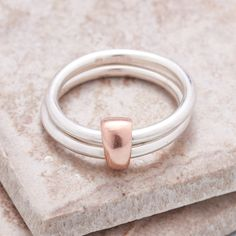 Handmade silver rings joined with a solid rose gold link to symbolise unity. Meaningful and wearable stacking ring handmade by Scarlett Jewellery in Hove.