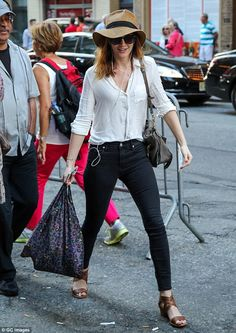 Summer style: She paired the charcoal jeans with a white linen shirt tucked in and brown sandals
