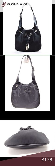"""Gucci Black Canvas Leather Trim Hobe bag Made In: Italy Canvas construction. Smooth leather trimmings. Silver-tone hardware. Flat top handle with buckle closure. Exterior drawstring detail. Open interior. Serial number: 001-4034-2123. Handle Length: 19.75"""" Handle Drop: 9.5"""" Height: 18"""" WITH HANDLE Length: 14"""" Width: Approximately 1.5""""  Gently Used It's in an excellent condition, hard to see used signs on leather. Interior and exterior both are clean. But there are scratches on the…"""