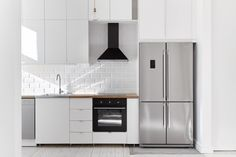 cocina blanca - azulejos blancos - encimera madera - tiradores discretos