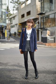 Navy coat on graphic tee, grey shorts, black tights and lace up boots.