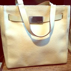 Vintage Cream Colored Calvin Klein Handle Bag This vintage light cream colored handle bag/tote is in excellent condition- the felt like fabric is spotless. This purse features a white/cream leather strap belted around the bag, just under the top, with the signature silver Calvin Klein logo serving as the front buckle, which opens to allow greater access to the bag. Closed, it cinches the top of the bag into a narrow opening & holds the shape of the bag. The leather belt matches the handles…