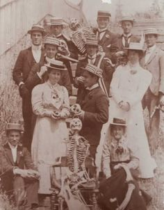 Group photo with skeletons, 1900s.  Look at the lady standing on the right!