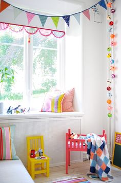 White walls, light wood floors, pops of bright color in garlands, pillows and furniture