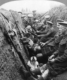 Scottish soldiers rest in a trench with their pet dog, 1915.