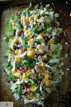 Asian Chicken Chop Salad...lettuce, cabbage, corn, chili, cilantro and avocado chunks topped with shredded chicken and homemade Mango Dressing