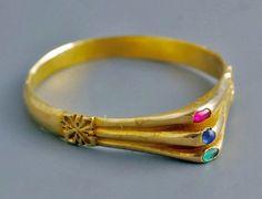 Bague médiévale en or à chaton triple. 13e siècle. La bague en or est de type « étrier ». L'anneau est plat à l'intérieur et convexe à l'extérieur. Sur chaque épaule est gravée une rosette à quatre feuilles. Le chaton est absolument exceptionnel, étant formé de trois chatons accolés, l'un serti d'un rubis de Ceylan, celui du centre d'un saphir de Ceylan et le troisième d'une émeraude.