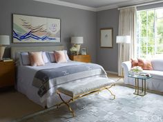 In the master bedroom, 1960s chests by Paul McCobb flank a bed topped with pillow shams by Matouk and an Hermès blanket; the bench is by Jan Showers Collection, the rug is by Jan Showers for Kyle Bunting, and the walls are painted in Benjamin Moore's Sea Haze.