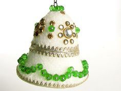 Sweet, vintage, handmade Christmas ornament has green and gold beads on a white styrofoam bell. The ornament has been decorated with gold trim