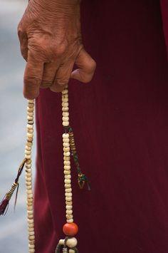 Tibetan monk prays with his #mala beads