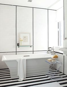 Love the stripe black and white marble floor and the narrow pencil black highlight tiles used on the wall in this modern bath