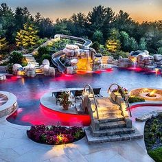 FULLY LOADED heated swimming pool with a hot-tub, lazy river, waterslide, island, bridge, infinity edge, cave, sunk in fire pit, waterfalls, AND customizable LED lighting. #ModernMansions