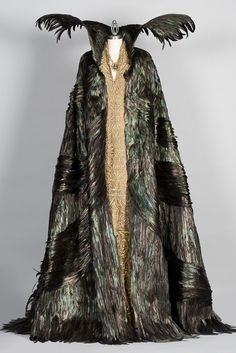 Snow White and the Huntsman, Costume designer: Colleen Atwood    Raven feather cape worn over a three-patterned gold embroidered dress - worn by Charlize Theron in the role of Queen Ravenna