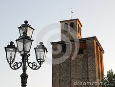 Photo made in Piove di Sacco a town in the province of Padua in the Veneto (Italy). In the image you see, in the foreground, a large city lamppost with four lamps. The lamppost and the great medieval tower, located in the middle of the market square, stand out both in the blue sky.