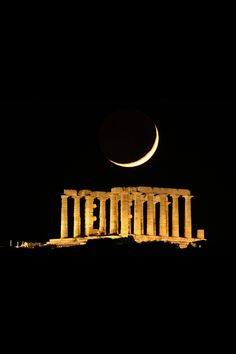 The Moon sets behind the temple of Poseidon at cape Sounio, Athens, Greece
