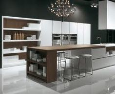 INSIDE white and wood kitchen with white shelves and steel hood ...