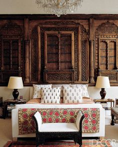 Decorator Matthew Patrick Smyth installed an 18th-century Moghul façade from a merchant's house as a headboard in the master bedroom of a documentaryfilmmaker client in London; the hand-blocked fabrics are from India, and the suzani is 19th century.