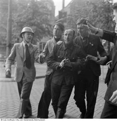 German soldier is arrested by Dutch citizens. The frightened German soldier is taken away, realizing that his days are over. Rokin, Amsterdam, The Netherlands (1945).