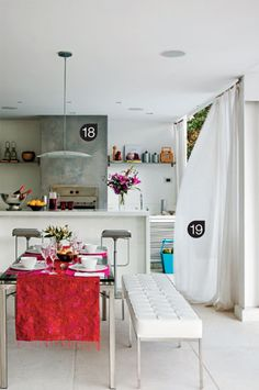 Para acomodar bem os convidados, há as banquetas Lem (Novo Ambiente) junto à churrasqueira e a mesa (Artefacto) com bancos estofados de couro branco (Way Contemporânea). Sobre o balcão, vaso de vidro com arranjos de flores de Duílio Sartori. O sofá tem almofadas coloridas (tecidos da Espaço Multi, confecção da AMSL). A do centro, com estampa, é da Beach & Country, assim como o garden seat azul. A toalha de mesa é da Área Objetos. A faixa de cimento queimado na parede (18) destaca a área da churr