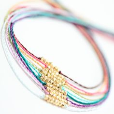beads strung on vibrantly colored hand twisted threads. Tie closure. These were created by ayofemlyjewelry an Etsy Shop.