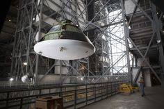 At NASA's Kennedy Space Center in Florida, the Orion ground test vehicle, or GTA, has been lifted high in the air by crane in the transfer a...