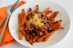 Melted cheese and meaty chili top sweet potato fries, for the best Chili Cheese Fries from the mountains to the sea.