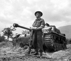 A soldier of the 2nd Lancashire Fusiliers, in front of a German StuG III which he knocked out with a PIAT, 1944.