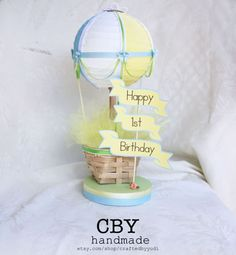 This listing is for (1) hot air balloon in Pastel Colors with CUSTOMIZABLE Flag  These adorable versions of our Hot Air Balloon Centerpieces feature a paper lantern and high quality ribbons and embellishments. These beauties would make a unique and beautiful addition to your next event and can be used as a focal point in any childs room or baby nursery. **DESCRIPTIONS** The 6 hand painted paper lantern has been decorated with ribbons and draping. The little bows are enhanced with a pearl…