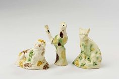 RARE STAFFORDSHIRE CREAMWARE TORTOISESHELL-GLAZED 'BIRD ON A STUMP' WHISTLE, AND TWO FIGURES OF A RECUMBENT LION AND SEATED CAT, 1780-1800.Height of first 3 7/8 inches.