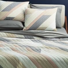 """<span class=""""copyHeader"""">diagonal dream.</span> Peaceful pieced bedding angles a fresh palette of tonal ivory, brown, grey and a pop of pink. In an elaborate process, 100% cotton panels are layered on a table, cut to size then hand-sewn together creating diagonal quilted channels. Part masculine, part feminine—palette plays nice in the master suite. Dreamy with our organic cement percale sheet set.<br /><br /><NEWTAG/><ul><li>Hand-sewn</li><li>100% cotton</li><li>Machine wash</li><li>Made…"""