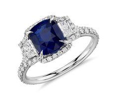 Luxuriously classic and chic, this three-stone ring features a timeless cushion cut sapphire set between two brilliant diamonds, all surrounded by pavé set diamonds set in 18k white gold.