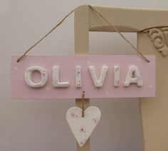 A beautiful hand painted personalised name sign with white floral ceramic letters finished with a floral hanging heart.You can make this sign truly unique and personal by spelling out a name or special message. The maximum number of letters is 9. If you have a particular colourway in mind, please get in touch as there are many other colour combinations that can be created. This personalised pretty room sign makes a truly unique gift, perfect for a new baby, Christening or birthday. The pale…
