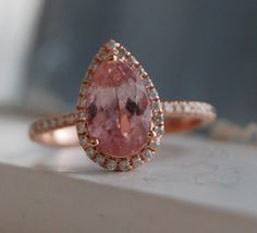 Peach sapphire ring by Eidelprecious. Pave engagement ring, diamond halo, pear cut sapphire, rose gold. #eidelprecious