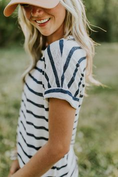 Searching for a comfy + casual addition to your wardrobe? Look no further! The navy + white Rita Stripe Tee is the ideal go-to top for any activity. A knit material creates a unique textured design while short sleeves with a dropped shoulder seem + rolled cuff hems add the perfect amount of detail. This truly is a must-have basic top.
